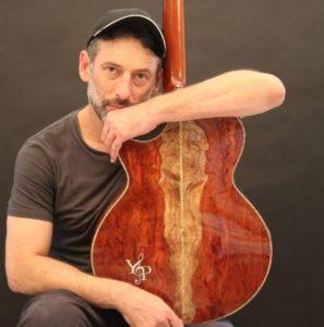 אמיר םרלמן מחזיק גיטרה בעיצוב שלו פרי ניסיון של שנות נגינה רבות